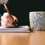 Woman writing in notebook with cup of hot drink next to her