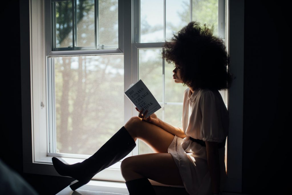 woman reading a book, silhouetted in a window